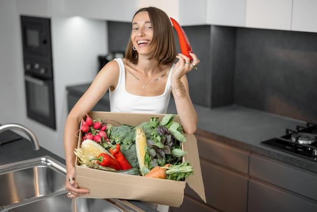 부엌에서 판지 상자에 포장된 신선한 야채를 가진 여자