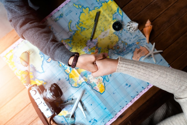 Woman with friend planning for vacation trip with accessories of traveler