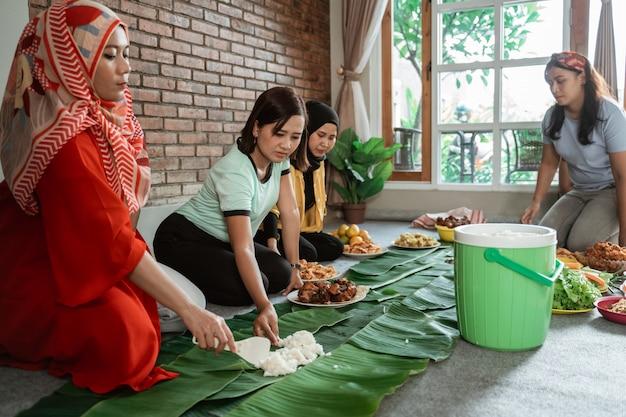 夕食のためにいくつかの食品を準備する友人を持つ女性