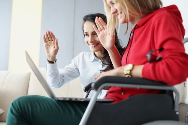 Woman with friend sitting in wheelchair and holding laptop waving to monitor