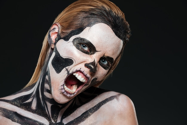 Woman with frightened halloween makeup and opened mouth shouting over black bakground