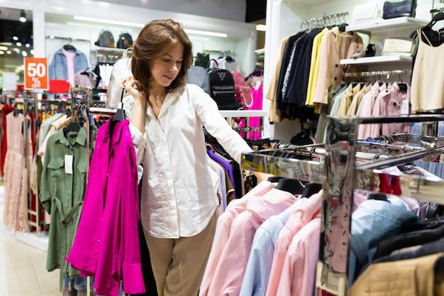 Женщина с блузкой цвета фуксии в руках в магазине одежды