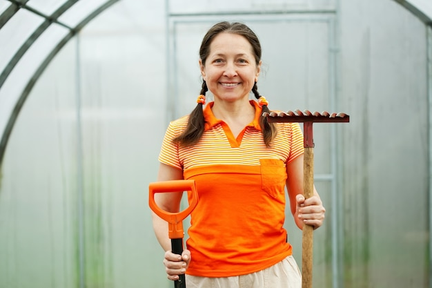 Woman with garden tools in greenhouse