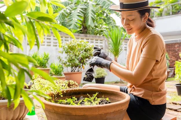 흙으로 정원 삽을 들고 식물 냄비 근처에 앉아 장갑을 낀 정원사를 가진 여자