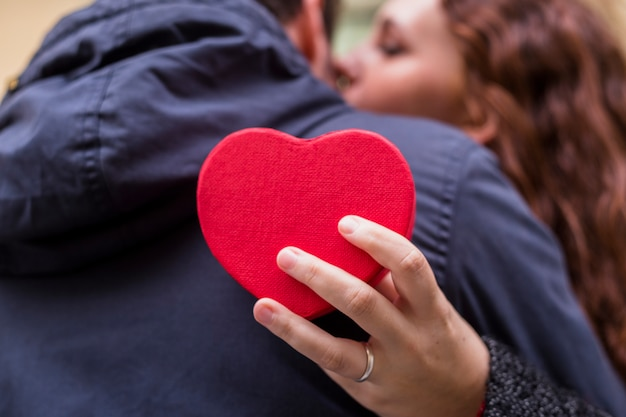 Woman with gift box in heart shape hugging man