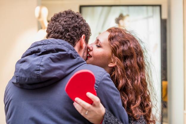 Woman with gift box kissing man on cheek