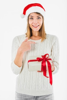 Woman with gift box pointing finger at herself