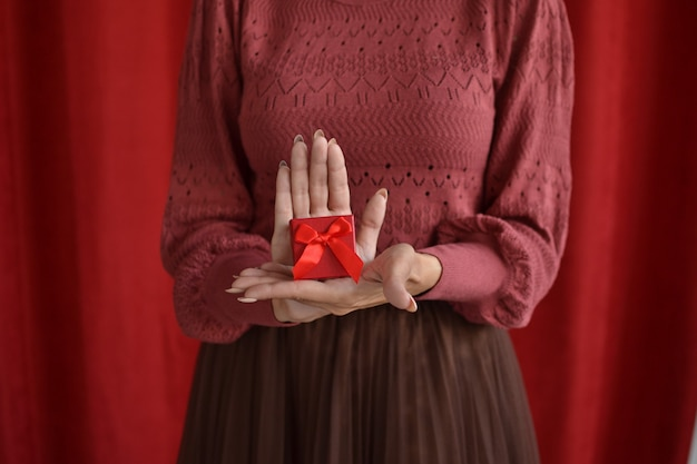 Woman with gift box on red background