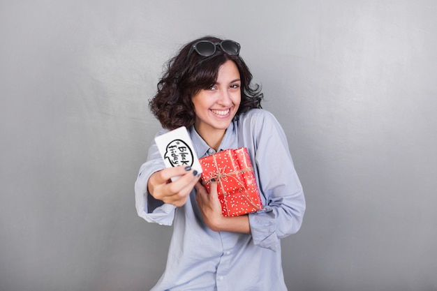 Woman with gift box showing credit card