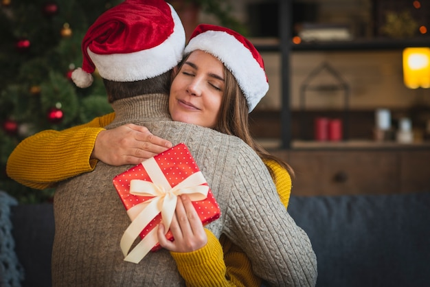 Woman with gift hugging man