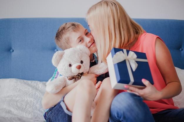 彼女の息子にキスする贈り物を持つ女性