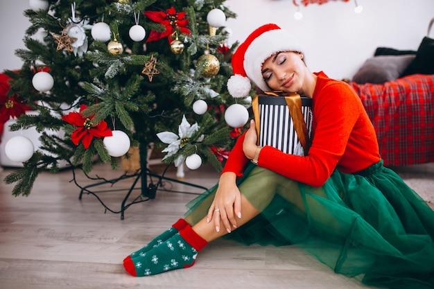 クリスマスツリーによる贈り物を持つ女性