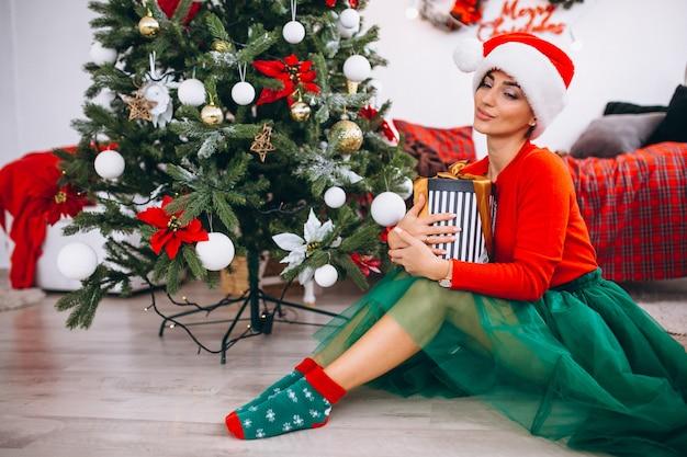 クリスマスツリーによるプレゼントを持つ女性