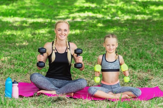 Женщина с девушкой тренируются в парке.