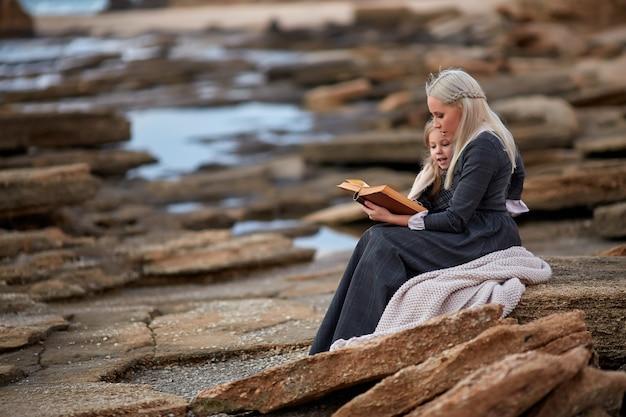 Женщина с книгой чтения девушки на побережье