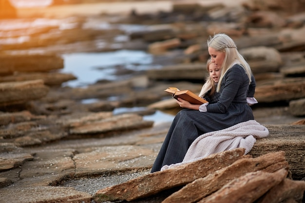 Woman with girl reading book on seashore
