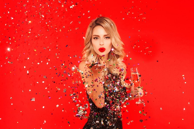 Woman with a glass of champagne celebrating new year party. portrait of beautiful smiling girl in shiny black dress throwing confetti