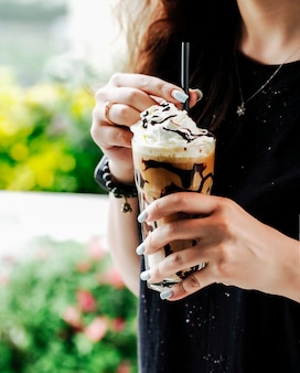 Woman with a glass of coffee smoothie with chocolate syrup and ice cream ball.
