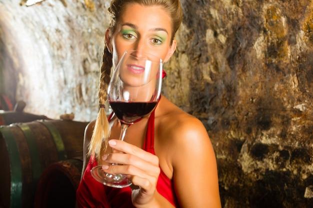 회의적으로 보는 와인의 유리를 가진 여자