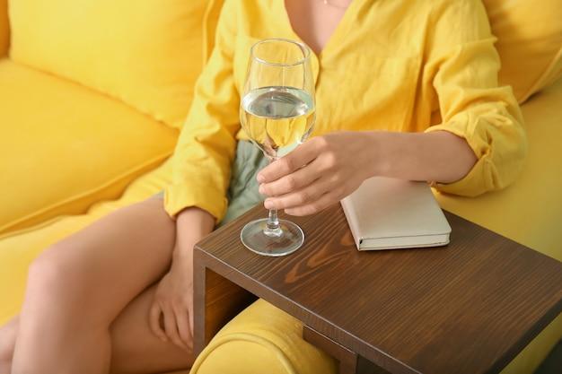 집에서 소파에 쉬고 와인 잔을 가진 여자