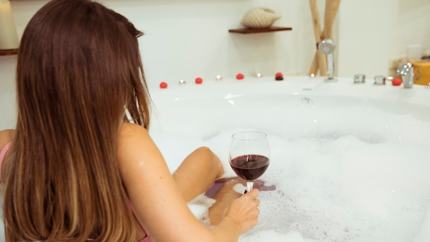 Woman with glass in spa tub with water and foam