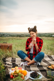 Woman with glass of wine, picnic on meadow