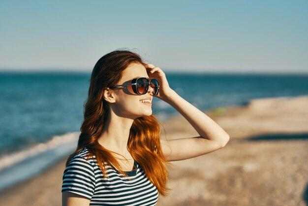 안경과 야외에서 머리 위에 손으로 몸짓을하는 여자 자른보기