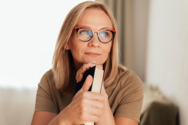 検疫中に本を保持している自宅で眼鏡をかけた女性