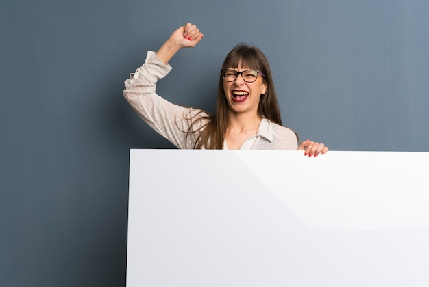 Woman with glasses over blue wall holding a placard for insert a concept