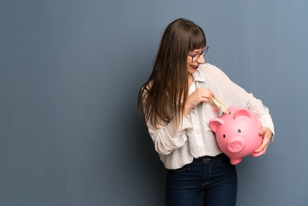 Woman with glasses over blue wall taking a piggy bank and happy because it is full