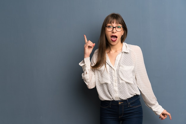 Woman with glasses over blue wall thinking an idea pointing the finger up