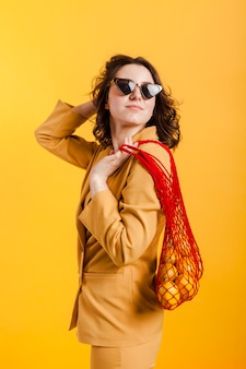 Woman with glasses carrying lemons