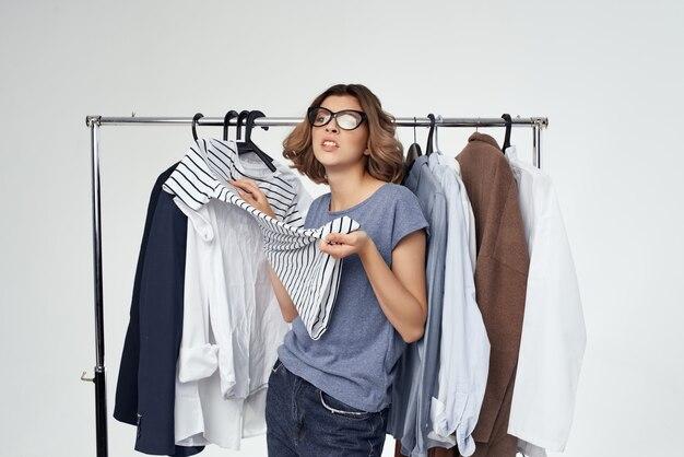 Женщина с вешалкой для одежды в очках, делая покупки на изолированном фоне
