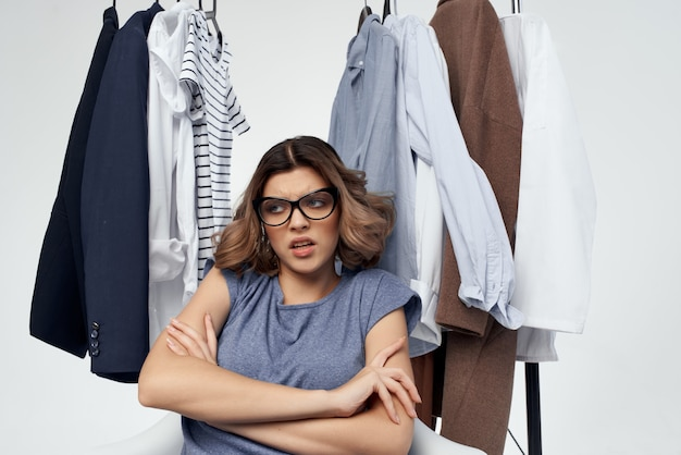 Woman with glasses clothes hanger shopping light background