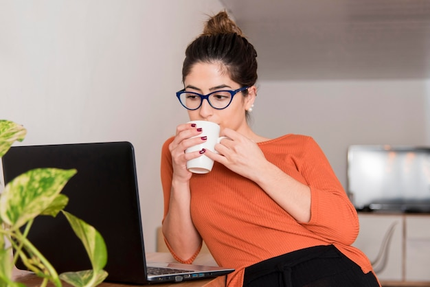 Woman with glasses drinking coffee