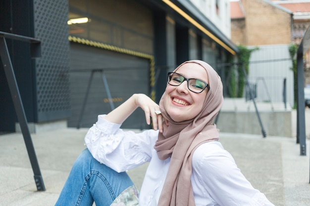 Woman with glasses and hijab smiling