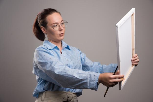 灰色の背景にキャンバスとブラシを保持しているメガネを持つ女性。高品質の写真