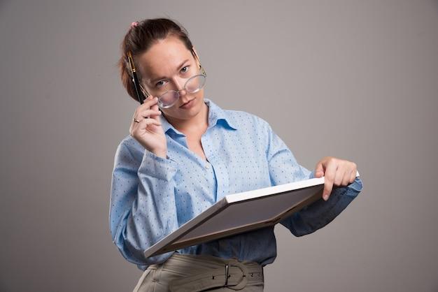 회색 배경에 캔버스와 브러시를 들고 안경 여자. 고품질 사진