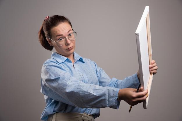 Donna con gli occhiali che tengono tela e pennello su grigio. foto di alta qualità