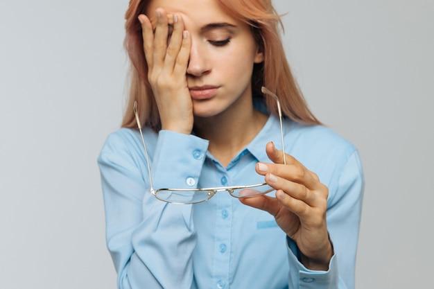 ノートパソコンでの作業後、目をこすることを保持している眼鏡の女性は疲れを感じています。