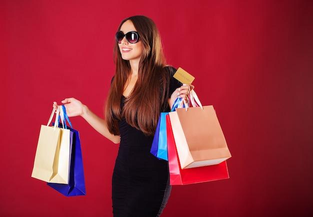 ショッピングバッグを保持している眼鏡の女性
