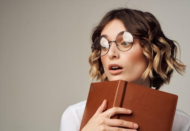 眼鏡をかけた女性は、灰色の短い髪型モデルで彼女の手に本を持っています