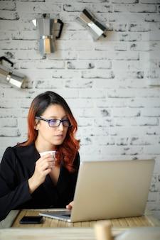 Женщина в очках держит чашку кофе