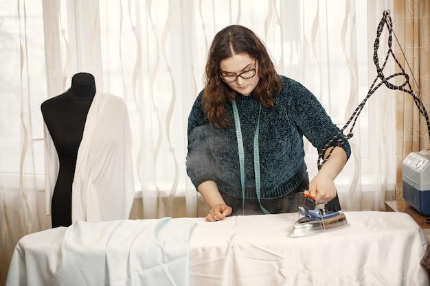 Женщина в очках. утюг для глажки одежды. швея шьет одежду.
