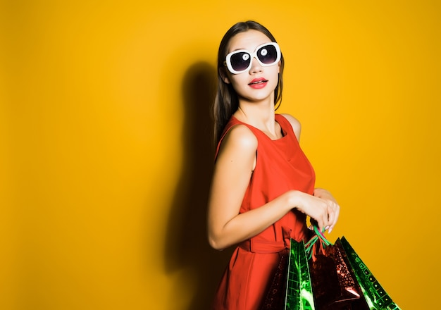 A woman with glasses is holding shopping bags