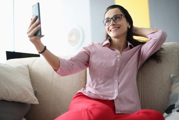 Женщина в очках сидит на диване, делая селфи
