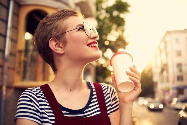 眼鏡をかけた女性が屋外で休暇の夏を歩く