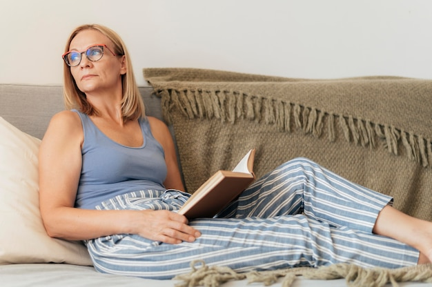 Woman with glasses reading book at home during quarantine