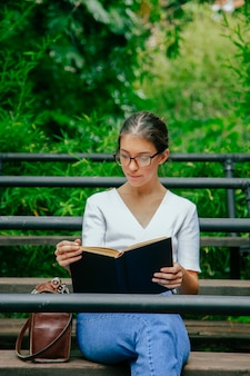 Woman with glasses reading a book outside