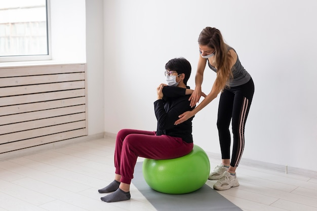 Woman with glasses recovering after having covid on fitness ball